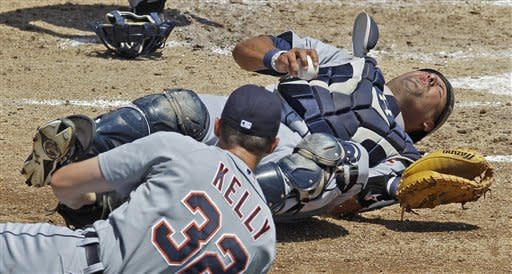 Detroit Tigers catcher Gerald Laird hangs onto the ball as he hits the dirt after colliding with first baseman Donny Kelly while chasing a foul by Baltimore Orioles Jai Miller in the second inning of a spring training baseball game in Sarasota, Fla., Friday, March 30, 2012. Laird sprained his left knee on the play. (AP Photo/Charles Krupa)