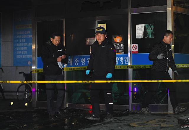 <p>Police investigators inspect the scene after a fire broke out at a hospital building after a fire broke out in Miryang on Jan. 26, 2018. (Photo: Jung Yeon-Je/AFP/Getty Images) </p>
