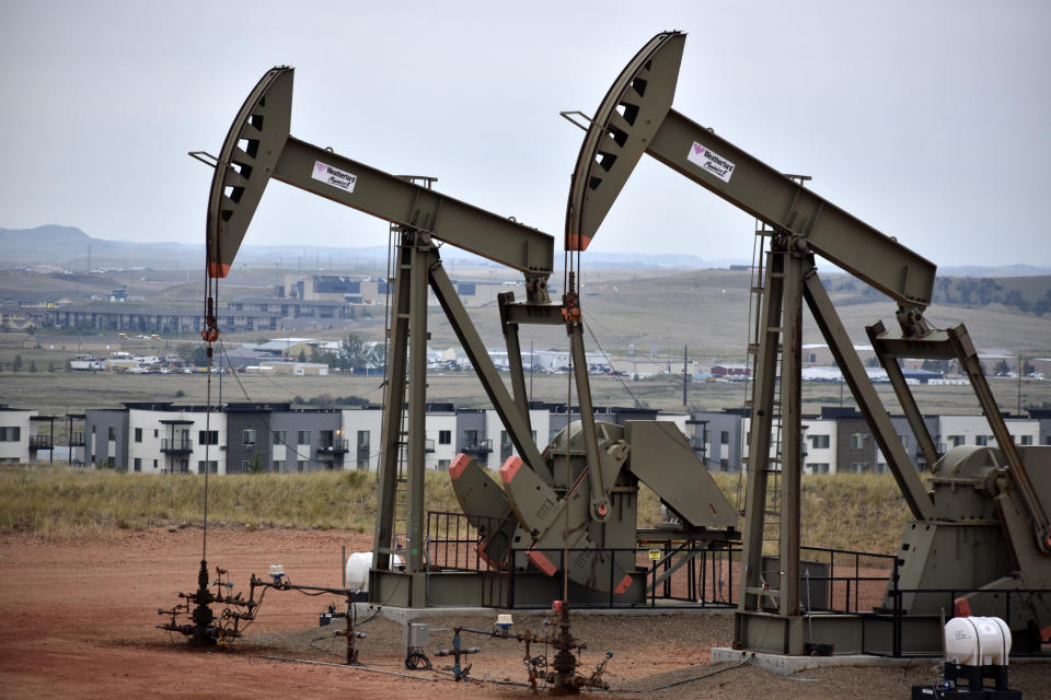 Pump jacks stand with apartments in the background Aug. 26, 2021, on the outskirts of Watford City, N.D., part of McKenzie County, the fastest-growing county in the U.S. That's according to new figures from the Census Bureau. (AP Photo/Matthew Brown)
