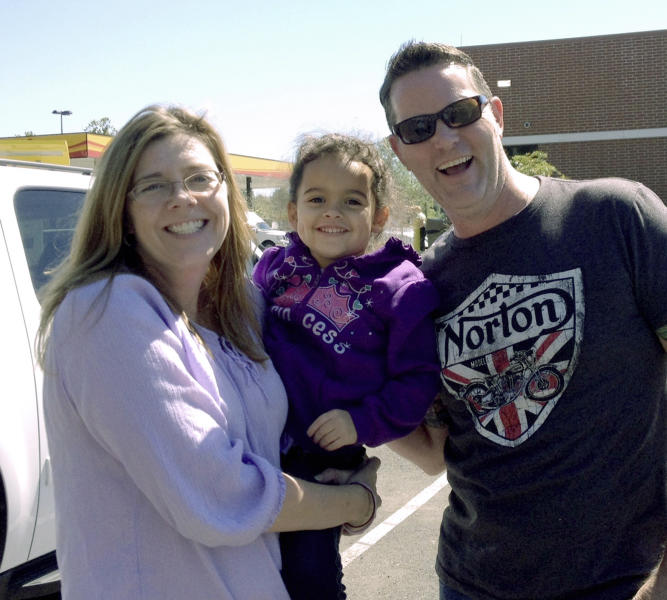 In this photo provided by the Capobianco Family, Veronica, center, the four-year-old Cherokee child at the center of a custody dispute spanning from Oklahoma to South Carolina, poses for a photo with her adoptive parents, Melanie Capobinco, left, and Matt Capobianco, at an undisclosed location Monday, Sept. 23, 2013, during their return trip to Charleston, South Carolina. Late Monday, the Oklahoma Supreme Court declined to uphold a stay keeping Veronica with her father, Dusten Brown, and ordered that custody be turned over the Capobiancos. (AP Photo/Capobianco Family Photo)