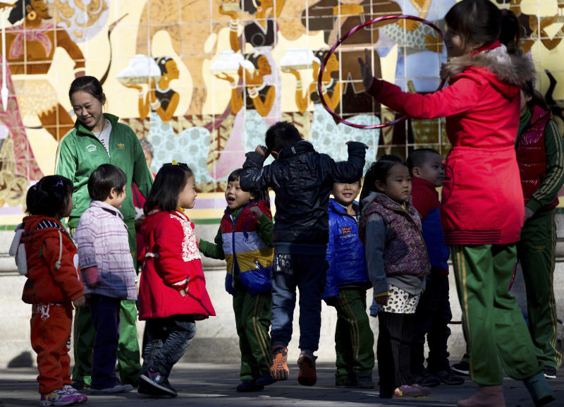 Kindergarten teachers play with children during an outdoor activity at the Ritan Park in Beijing Wednesday, Oct. 31, 2012. A government think tank says China should start phasing out its one-child policy immediately and allow two children for every family by 2015. It remains unclear whether Chinese leaders are ready to take that step. (AP Photo/Andy Wong)