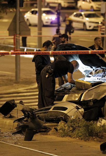 Israeli policemen inspect a car after it rammed a group of pedestrians at the Ammunition Hill tram stop in Jerusalem on October 22, 2014 (AFP Photo/Ahmad Gharabli)