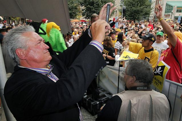 Pittsburgh Pirates manager Clint Hurdle, left, takes pictures of a lunchtime pep rally in downtown Pittsburgh held in support of his post-season bound Pittsburgh Pirates, Monday, Sept. 30, 2013. In their first taste of post-season baseball action since 1992, the Pirates will play the Cincinnati Reds Tuesday in Pittsburgh in the National League Wild Card baseball game. The winner will face the St. Louis Cardinals in the NLDS starting Thursday in St. Louis. (AP Photo/Gene J. Puskar)