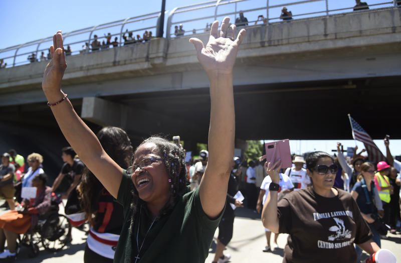 """Lavonne Green, left, yells """"Hallelujah! Hallelujah!"""" as protestors walk on the Dan Ryan Expressway, Saturday, July 7, 2018, in Chicago. The protesters shut down the expressway to draw attention to the city's gun violence and pressure public officials to do more to help neighborhoods hardest hit by it.(AP Photo/Annie Rice)"""
