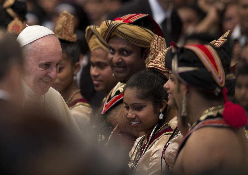 Pope Francis greets Sri Lankan dancers who performed during a mass for their community in St. Peter's Basilica at the Vatican, Saturday, Feb. 8, 2014. (AP Photo/Alessandra Tarantino)
