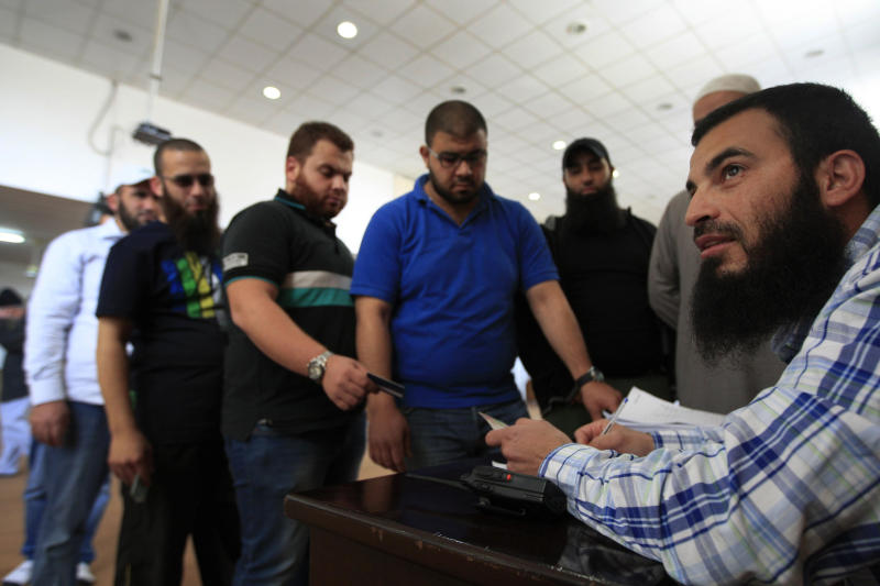 Lebanese Sunni Muslim men queue as they register their names for jihad in Syria, at a mosque in the southern port city of Sidon, Lebanon, Tuesday April 23, 2013. Lebanese Sunni Muslim clerics Ahmad Al-Assir and Sheikh Salem al-Rafie called late Monday for jihad in Syria to protect Sunnis in villages under attack by Syrian troops and pro-government Shiite gunmen. Lebanon and Syria share a complex web of political and sectarian ties and rivalries which are easily enflamed. Lebanon, a country plagued by decades of strife, has been on edge since the uprising in Syria against President Bashar Assad began in March 2011, with deadly clashes between pro and anti- Assad Lebanese groups erupting on several occasions. (AP Photo/Mohammed Zaatari)