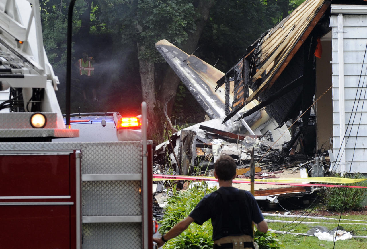 A firefighter surveys the scene of a small plane crash, Friday, Aug. 9, 2013, in East Haven, Conn. The multi-engine, propeller-driven plane plunged into a working-class suburban neighborhood near Tweed New Haven Airport, on Friday. (AP Photo/Fred Beckham)