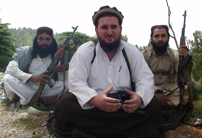 """In this photo taken Aug. 6, 2012 Pakistani Taliban spokesman Ahsanullah Ahsan, center, flanked by his body guards talks to The Associated Press in the militant group's stronghold of Shawal in Pakistani tribal region of South Waziristan. The Taliban have threatened to kill a Pakistani cricket star who has become a major political player if he holds a planned march to their tribal stronghold along the Afghan border to protest U.S. drone attacks. Ahsan said """"If he comes, our suicide bombers will target him,"""" (AP Photo/ Ishtiaq Mahsud)"""