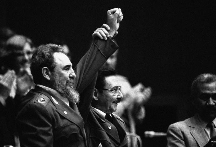 FILE - In this Feb. 8, 1986 file photo, Cuban President Fidel Castro, left, joins hands with his younger brother Raul Castro, chief of the Cuban Armed Forces and first vice president, after the two were reelected during the 3rd Cuban Communist Party Congress session in Havana, Cuba. For most of his life, Raul Castro played second-string to his brother, but for the past decade, it's Raul who's been the face of communist Cuba. On Friday, April 16, 2021, Raul Castro formally announced he'd step down as head of the Communist Party, leaving Cuba without a Castro in an official position of command for the first time in more than six decades. (AP Photo/Charles Tasnadi, File)