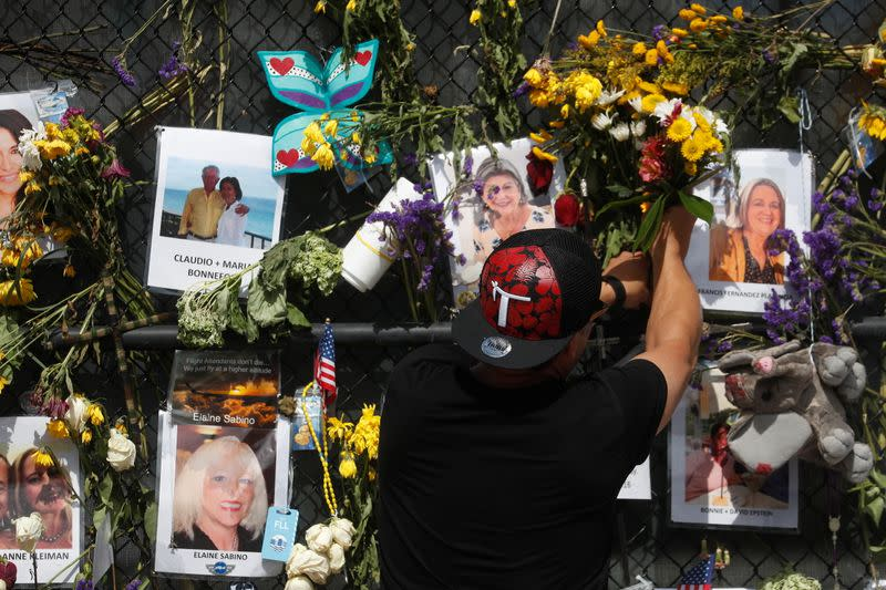 A man places flowers on a makeshift memorial for the victims of the Surfside's Champlain Towers South condominium collapse in Miami, Florida