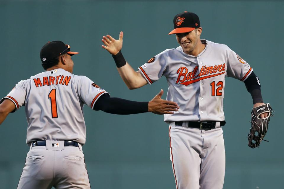 Baltimore Orioles' Stevie Wilkerson (12) celebrates with Richie Martin (1) after making the catch on a flyout by Boston Red Sox's Jackie Bradley Jr. during the eighth inning of a baseball game in Boston, Sunday, Sept. 29, 2019. (AP Photo/Michael Dwyer)
