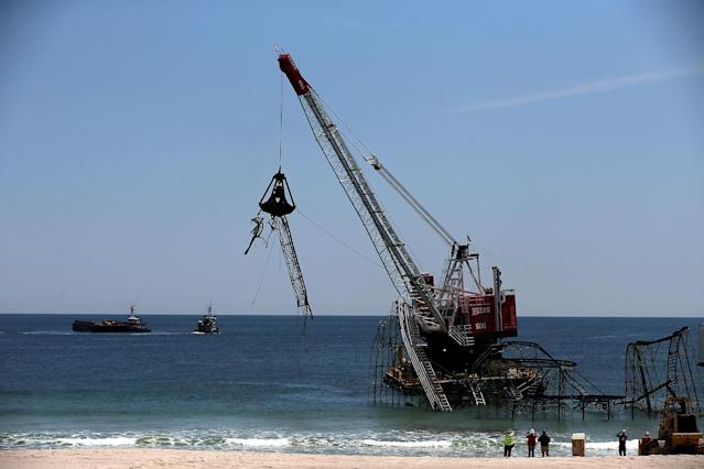 SEASIDE HEIGHTS, NJ - MAY 14: A large crane starts to demolish the Star Jet roller coaster that has been in the ocean for six months after the Casino Pier is sat on collapsed when Superstorm Sandy hit, May 14, 2013 in Seaside Heights, New Jersey. The Casino Pier has contracted Weeks Marine to remove the Jet Star roller coaster from the Atlantic Ocean. (Photo by Mark Wilson/Getty Images)