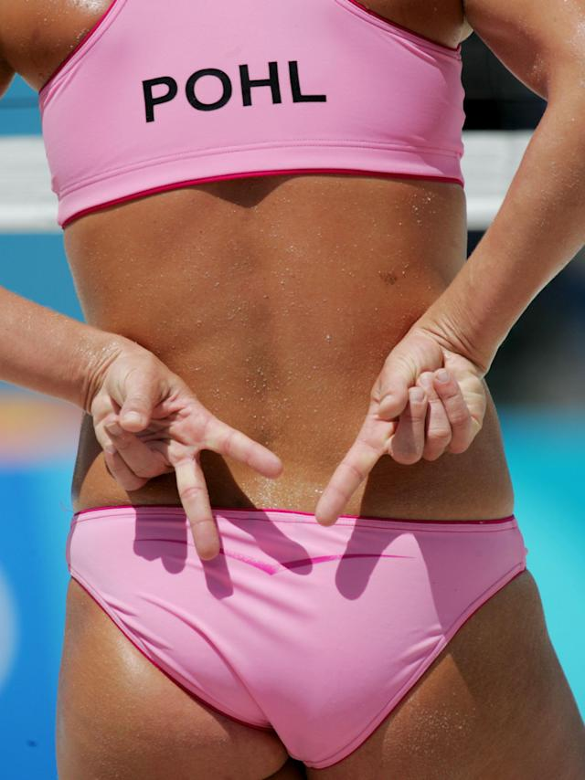 Germany's Stephanie Pohl hides her hands behind her back as she sends a signal to her partner Okka Rau during their match at the Olympic Beach Volleyball Centre in Athens, Greece on Saturday, Aug. 14, 2004. The German team beat China's Lu Wang and Wenhui You in two sets, 21-17 and 21-18. (AP Photo/Dave Martin)