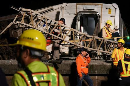 Workers walk around derailed train as they prepare to clear the accident site, in Yilan, Taiwan October 21, 2018. Picture taken October 21, 2018. REUTERS/Lee Kun Han