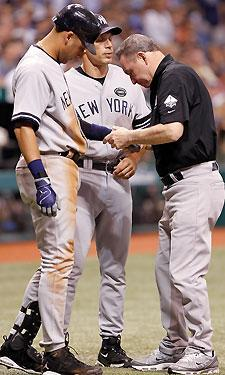 Yankees shortstop Derek Jeter (L) receives treatment for a pitch that didn't even hit him