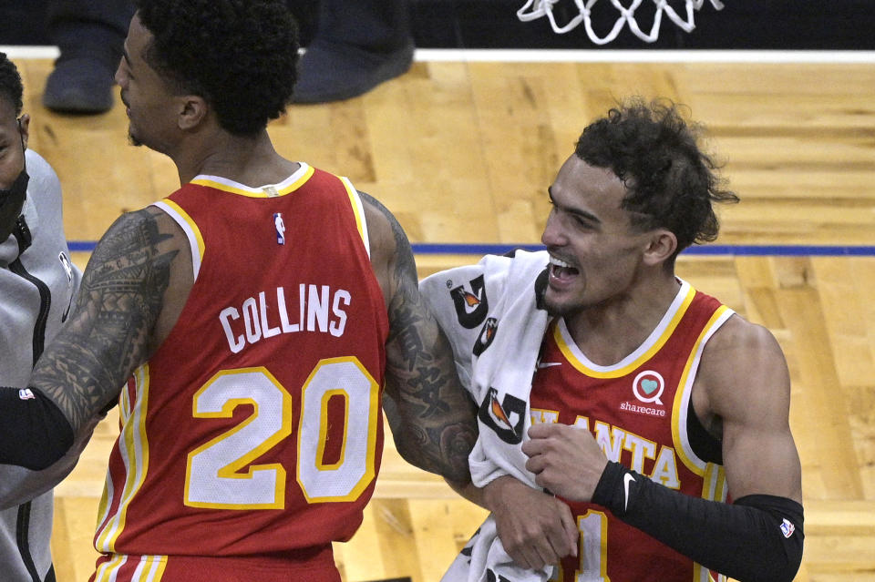 Atlanta Hawks forward John Collins (20) and guard Trae Young, right, celebrate the team's win over the Orlando Magic in an NBA basketball game Wednesday, March 3, 2021, in Orlando, Fla. (AP Photo/Phelan M. Ebenhack)