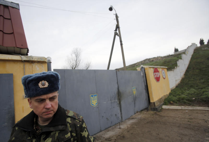 A Ukrainian officer stands outside the gate of a military base at the Black Sea port of Sevastopol in Crimea, Ukraine, Saturday, March 8, 2014. A Ukrainian officer at the military base said that pro-Russia soldiers crashed a truck through its gates late on Friday in an attempt to take it over. (AP Photo/Darko Vojinovic)