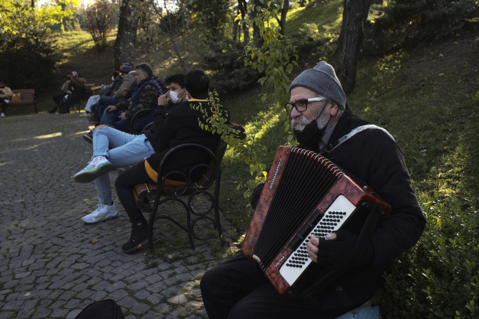 A musician performs in a public garden, in Ankara, Turkey, Friday, Nov. 27, 2020. When Turkey changed the way it reports daily COVID-19 infections, it confirmed what medical groups and opposition parties have long suspected — that the country is faced with an alarming surge of cases that is fast exhausting the Turkish health system. The official daily COVID-19 deaths have also steadily risen to record numbers in a reversal of fortune for the country that had been praised for managing to keep fatalities low. With the new data, the country jumped from being one of the least-affected countries in Europe to one of the worst-hit.(AP Photo/Burhan Ozbilici)