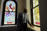 In this May 28, 2021, photo, Rev. Robert R.A. Turner, pastor of the historic Vernon African Methodist Episcopal Church, looks at a stained glass window while giving a tour of the church to a missionary around centennial commemorations of the Tulsa Race Massacre in Tulsa, Okla. Only the basement remained of the church, partially destroyed in the massacre in 1921 that destroyed the area known as Black Wall Street. (AP Photo/John Locher)