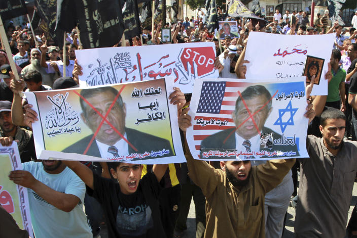 """FILE - In this Friday, Sept. 14, 2012 file photo, Palestinian Islamic Jihad supporters rally with banners depicting Morris Sadek during a protest in Khan Younis, southern Gaza Strip, as part of widespread anger across the Muslim world about a film ridiculing Islam's Prophet Muhammad. The banners in Arabic read, """"Death to Israel,"""" """"death to America"""" and, """"anyone but God's Prophet."""" An Egyptian court on Wednesday, Nov. 28, 2012 has convicted in absentia seven Egyptian Coptic Christians and a Florida-based American pastor and sentenced them to death on charges linked to an anti-Islam film that had sparked riots in parts of the Muslim world. (AP Photo/Adel Hana, File)"""