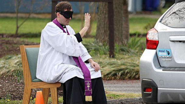 PHOTO: Father Scott Holmer, of St. Edward the Confessor Catholic Church, makes the sign of the cross while holding confession in the church parking lot, on March 20, 2020, in Bowie, Md. (Rob Carr/Getty Images)