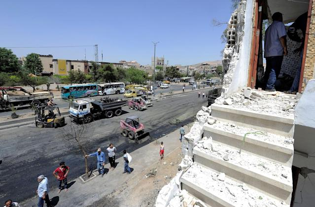 <p>People inspect the damage at a blast site in the Baytara traffic circle near the Old City of Damascus, Syria July 2, 2017. (Omar Sanadiki/Reuters) </p>