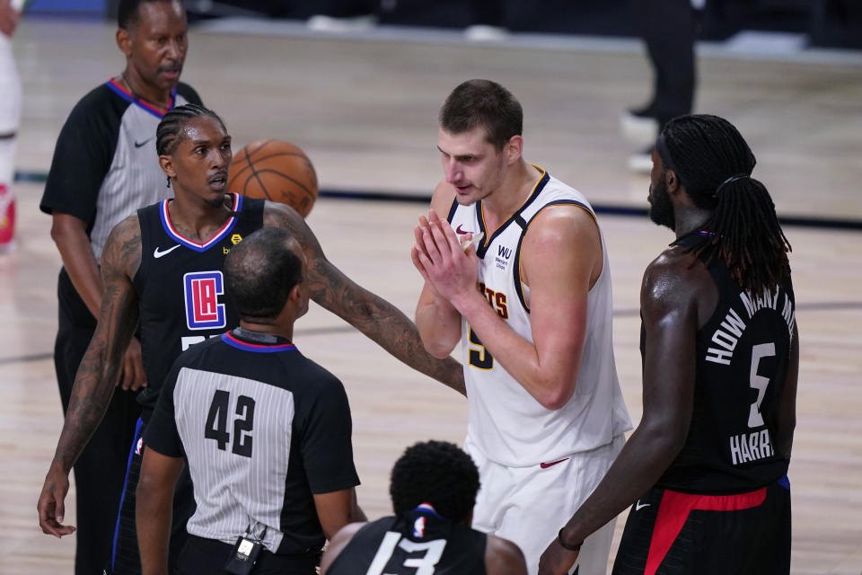 Denver Nuggets center Nikola Jokic, center, questions a call during the second half of an NBA conference semifinal playoff basketball game against the LA Clippers, Tuesday, Sept. 15, 2020, in Lake Buena Vista, Fla. (AP Photo/Mark J. Terrill)