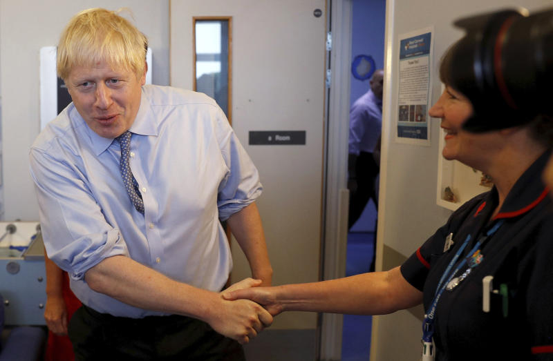 Britain's Prime Minister Boris Johnson meets with patients and nursing staff at the Royal Cornwall Hospital in Truro, England, Monday Aug. 19, 2019.   Johnson is under increasing pressure Monday to recall Parliament after leaked government documents warned of widespread problems if the U.K. leaves the European Union without a Brexit withdrawal agreement. (Peter Nicholls/Pool via AP)