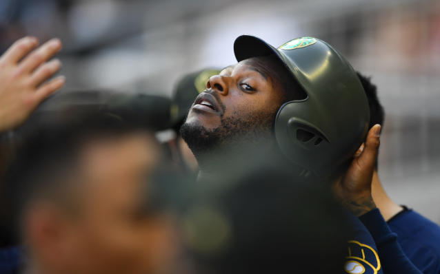Milwaukee Brewers' Lorenzo Cain is congratulated in the dugout after scoring during the first inning of the team's baseball game against the Atlanta Braves, Saturday, May 18, 2019, in Atlanta. (AP Photo/John Amis)
