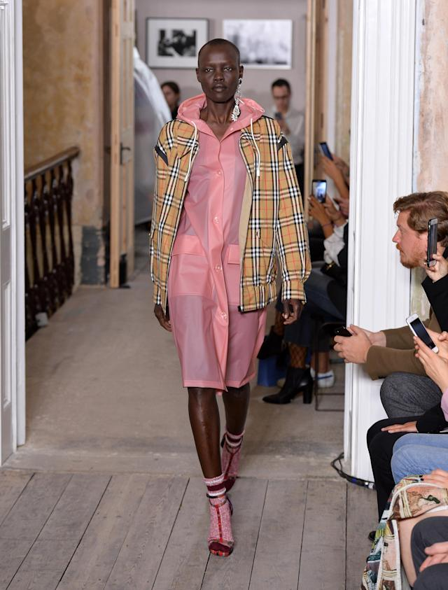 Model wears a millennial pink rain coat and Burberry check zip-up jacket at the brand's September 2017 show. (Photo: Getty Images)