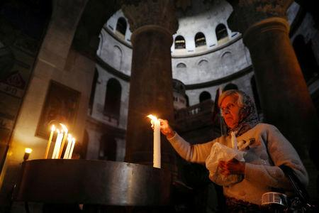 FILE PHOTO: A worshipper lights a candle as she visits the Church of the Holy Sepulchre in Jerusalem's Old City January 22, 2018. REUTERS/Ammar Awad/File Photo