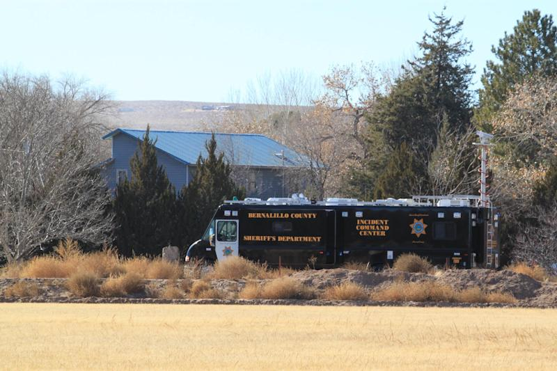 A Bernalillo County Sheriff's Department crime lab is stationed outside a home south in Albuquerque, N.M., on Sunday, Jan. 20, 2013, where two adults and three children were found shot to death. Authorities say a teenager has been arrested and booked on murder and other charges in connection with the shootings. (AP Photo/Susan Montoya Bryan)