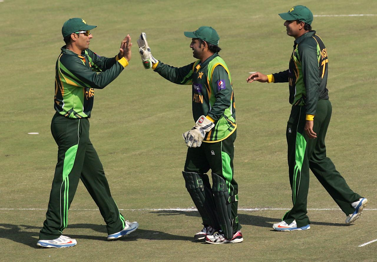 Pakistan captain Misbah Ul Haq celebrates a wicket with keeper Sarfraz Ahmed during the 2nd game of the three match ODI cricket series between Pakistan and hosts Zimbabwe at the Harare Sports Club August 29, 2013.AFP PHOTO / JEKESAI NJIKIZANA        (Photo credit should read JEKESAI NJIKIZANA/AFP/Getty Images)