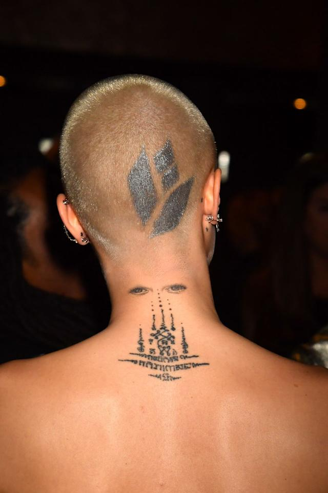 """<p>Though this tattoo wasn't permanent, Cara got her head inked after she shaved it bald for her part in the movie <em>Life in a Year</em>. The """"tattoo"""" was actually a drawing designed by hairstylist, Mara Roszak, and featured geometric figures shaped into what kind-of looks like a flower. </p>"""