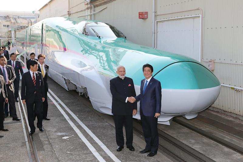 India's Prime Minister Narendra Modi (2nd R) and his Japanese counterpart Shinzo Abe (R) shake hands in front of a shinkansen train during their inspection at a bullet train manufacturing plant in Kobe, Hyogo prefecture on November 12, 2016: JIJI PRESS/AFP/Getty Images
