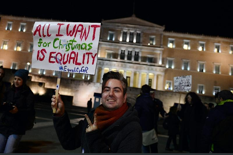 """A man holds a sign reading """"All I want for Christmas is equality"""" during a demonstration outside the Greek parliament in Athens on December 22, 2015 (AFP Photo/Louisa Gouliamaki)"""