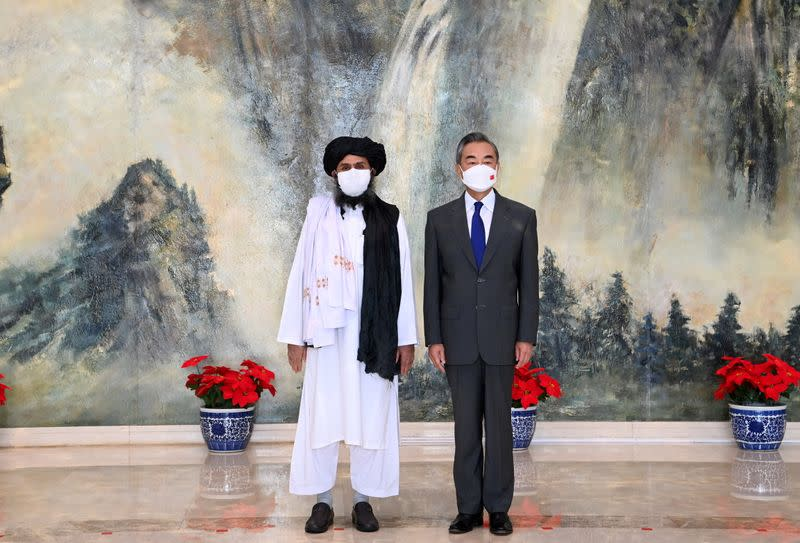 FILE PHOTO: Chinese State Councilor and Foreign Minister Wang Yi meets with Mullah Abdul Ghani Baradar, political chief of Afghanistan's Taliban, in Tianjin