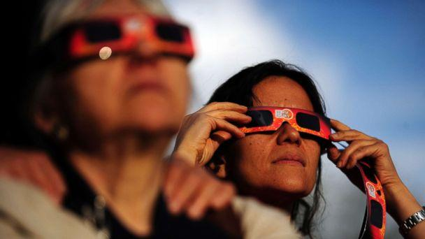 PHOTO: Ina Schakaraschwili holds her glasses in place during a solar eclipse at the University of Denver's Chamberlain Observatory in this May 20, 2012 file photo (AAron Ontiveroz/The Denver Post via Getty Images)