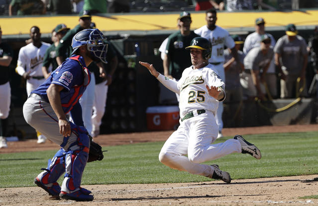 Oakland Athletics' Stephen Piscotty (25) slides in to home to score the winning run as Texas Rangers catcher Isiah Kiner-Falefa, left, waits for the throw during the ninth inning of a baseball game in Oakland, Calif., Wednesday, April 24, 2019. (AP Photo/Jeff Chiu)