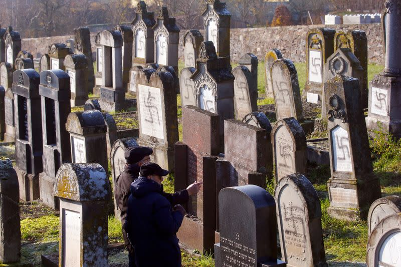 Two men stand in front of graves desecrated with swastikas at the Jewish cemetery in Westhoffen