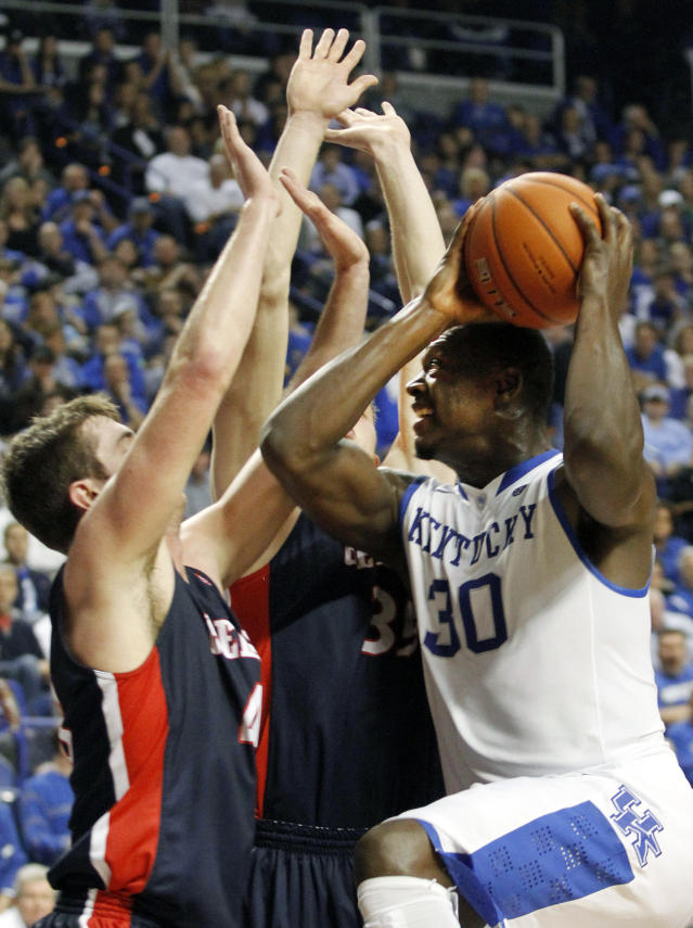 Kentucky's Julius Randle (30) looks for an opening between Belmont's Jeff Laidig and Evan Bradds during the first half of an NCAA college basketball game, Saturday, Dec. 21, 2013, in Lexington, Ky. (AP Photo/James Crisp)