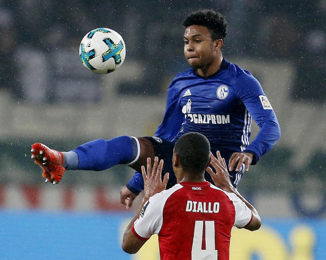 Mainz's Abdou Diallo, bottom, and Schalke's Weston McKennie challenge for the ball during a German first division Bundesliga soccer match between FSV Mainz 05 and FC Schalke 04 in Mainz, Germany, Friday, March 9, 2018.(AP Photo/Michael Probst)