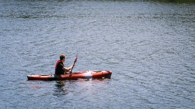A young man wearing a life jacket paddles in his kayak on the Gatineau side of the Ottawa River on May 15, 2021.