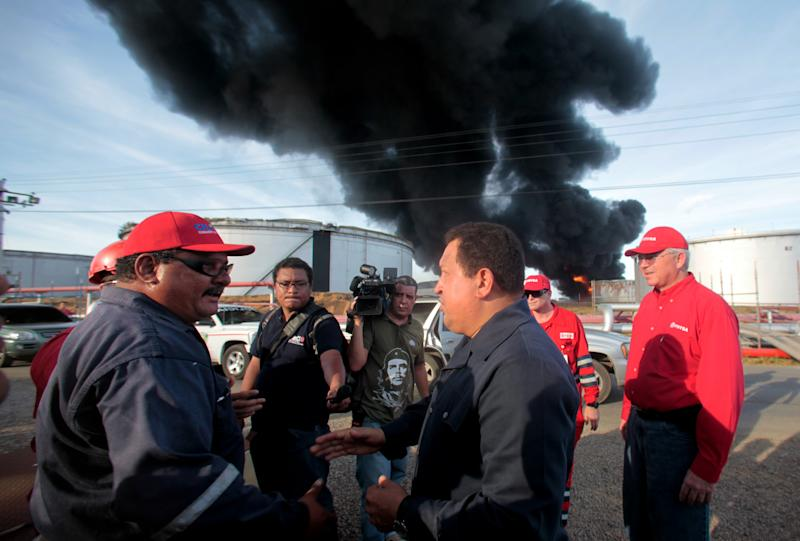 In this photo provided by Miraflores Presidential Press Office, Venezuela's president Hugo Chavez, right center, speaks with a worker during a visit to the Amuay refinery near Punto Fijo, Venezuela, Sunday, Aug. 26, 2012. A powerful explosion rocked Venezuela's biggest oil refinery early Saturday killing at least 39 people and injuring more than 80 in Venezuela's deadliest refinery blast ever.(AP Photo/Miraflores Presidential Office)
