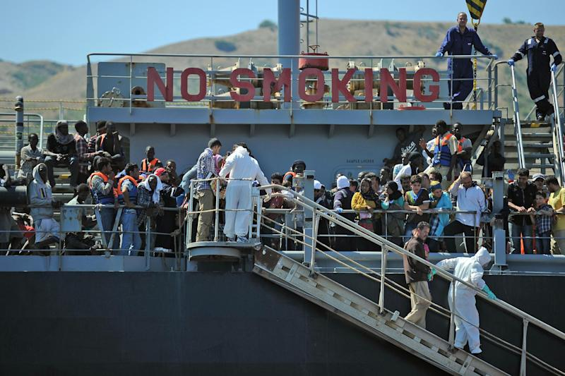 """Immigrants are transferred from the tanker """"Torm Lotte"""" to the tug boat """"Grifone"""" near Messina following a rescue operation on July 20, 2014"""