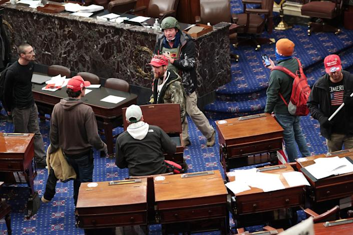 Protesters, including Larry Brock in back, enter the Senate Chamber on January 06, 2021 in Washington, DC. Congress held a joint session today to ratify President-elect Joe Biden's 306-232 Electoral College win over President Donald Trump. Pro-Trump protesters have entered the U.S. Capitol building after mass demonstrations in the nation's capital.