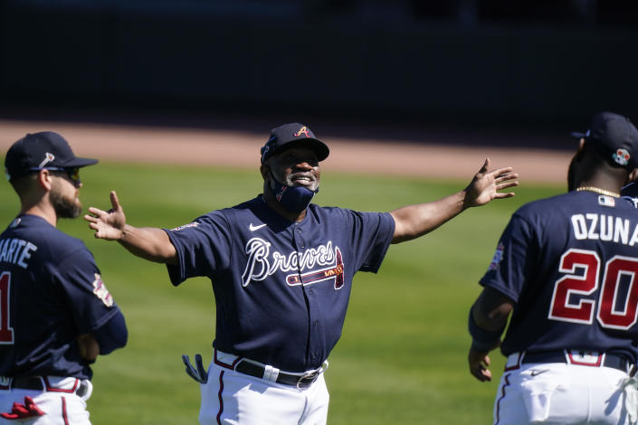 Atlanta Braves first base coach Eric Young talks with Marcell Ozuna (20) and Ender Inciarte (11) during spring training baseball practice on Tuesday, Feb. 23, 2021, in North Port, Fla. (AP Photo/Brynn Anderson)