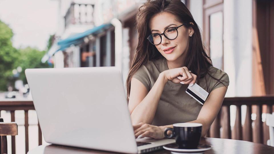 Businesswoman using laptop and credit card.