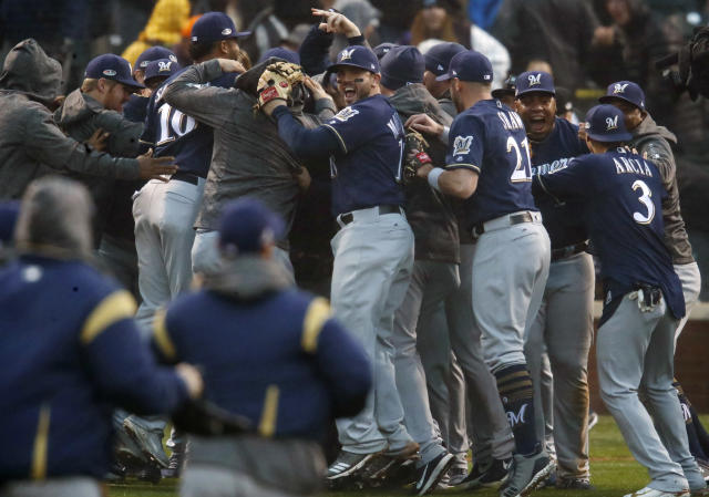 Milwaukee Brewers third baseman Mike Moustakas, back center, joins teammates in celebrating after the final out in the ninth inning of Game 3 of a baseball National League Division Series against the Colorado Rockies Sunday, Oct. 7, 2018, in Denver. The Brewers won 6-0 to sweep the series in three games and move on to the National League Championship Series. (AP Photo/David Zalubowski)