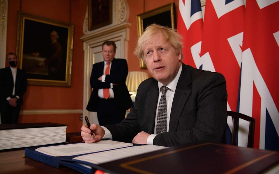Lord Frost, the minister in charge of UK-EU relations, looks on as Boris Johnson signs the trade deal with the EU in December last year.  - AFP